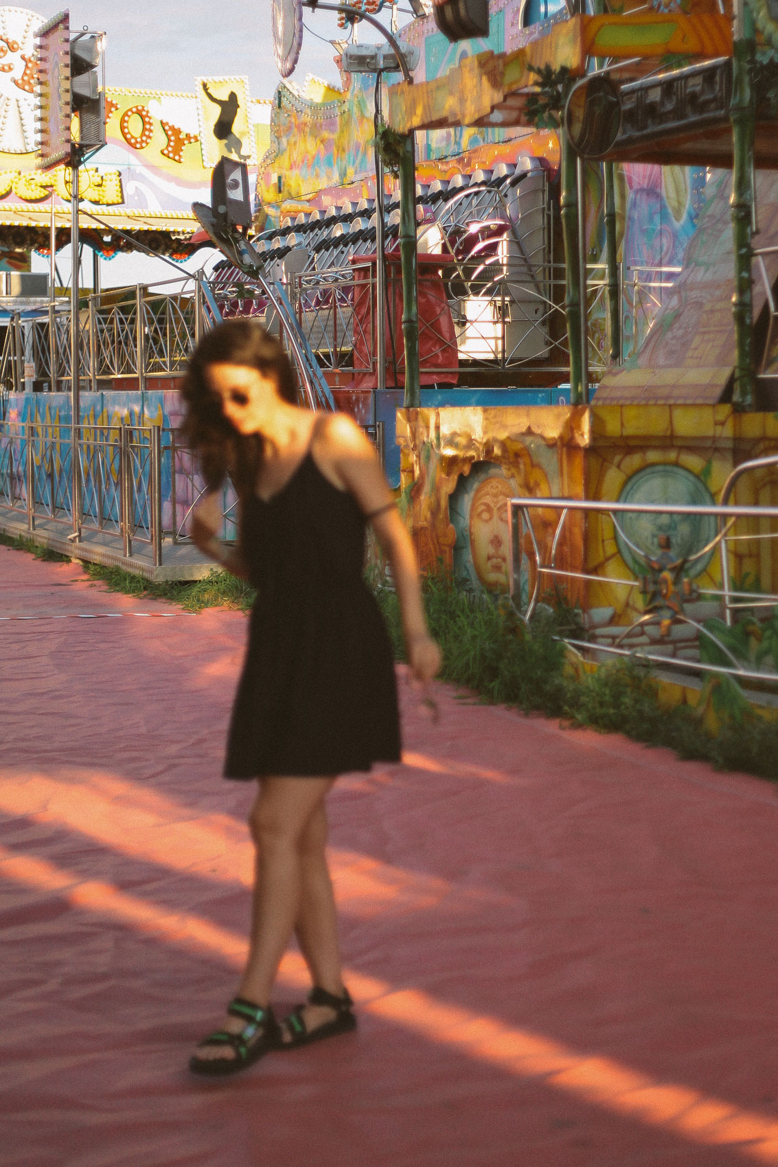 sunset at a funfair with a girl in a black dress in front of the scene